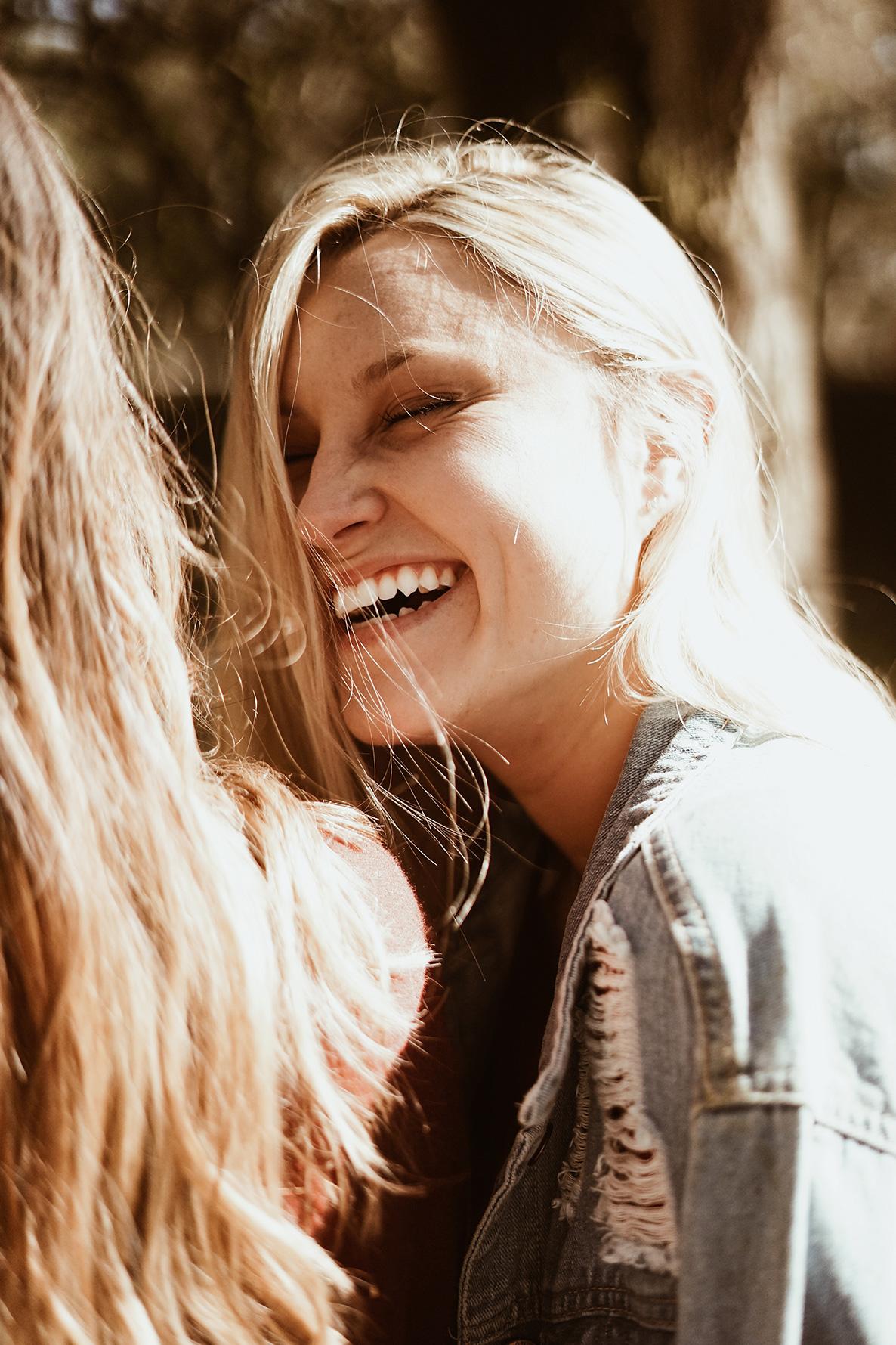 lachende Frau die gesunde Zaehne zeigt
