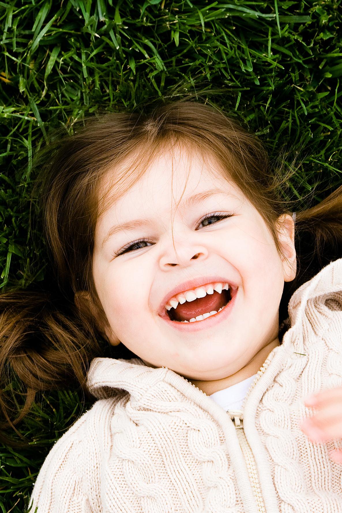 kleines Maedchen laechelt und zeigt Zaehne, Sinnbild fuer Kinderzahnheilkunde